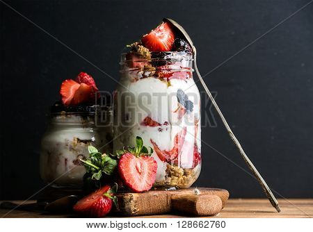 Yogurt oat granola with strawberries, mulberries, honey and mint leaves in tall and small glass jars on black backdrop, selective focus, copy space