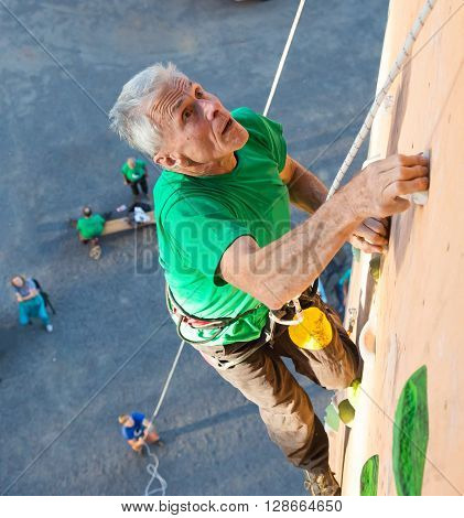 Elderly Male Climber Makes Hard Move and Looking High Up on Outdoor Climbing Wall Sport Competitions Very Emotional Face Belaying Partner Fans Staying Remote Ground