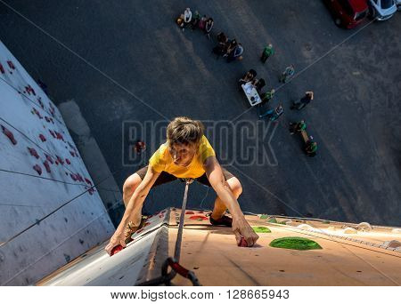 Elderly Female Climber Makes Hard Move and Looking High Up on Outdoor Climbing Wall Sport Competitions Very Emotional Face Belaying Partner Fans Staying Remote Ground