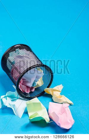 Office Trash Bin With Crumpled Color Paper Over The Blue Background