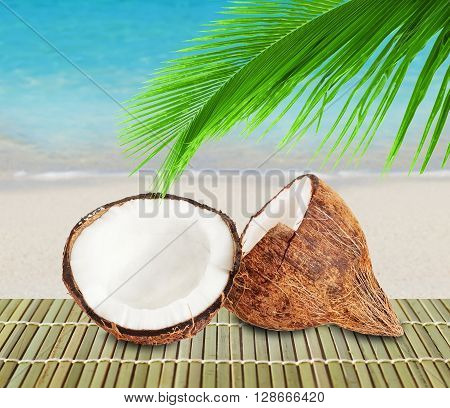 Two halves of coconut and green palm leaf on a beach background. White sand and crystal blue water of ocean.