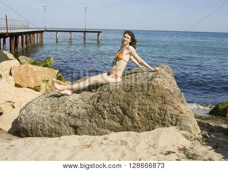 Young European woman with brown hair in bikini sits on big stone on sea shore pier behind.