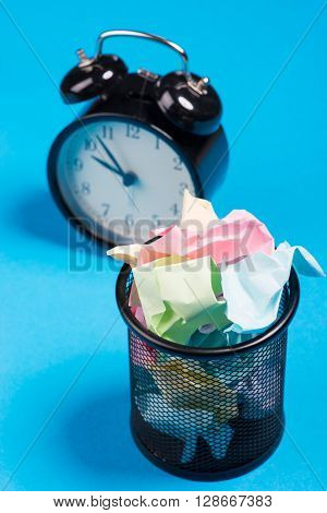 Office Trash Bin With Crumpled Color Paper And Alarm Clock Over The Blue Background
