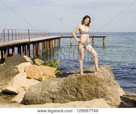 Young European woman in bikini stands on big stone on sea beach.
