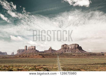 panoramic view of desert highway toward monument valley