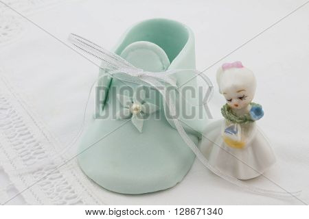 Blue fondant baby booty next to little lady porcelain figurine isolated on white lace