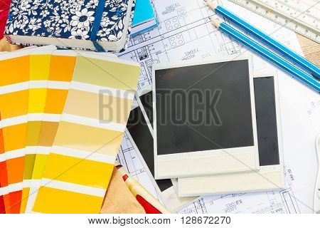 Interior designer's working table, an architectural plan of the house,  color palette guide and fabric samples in yellow shades, copy space on instant empty photos