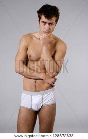Silhouette of young adult sleepy man naked muscular torso in white panties isolated on grey background