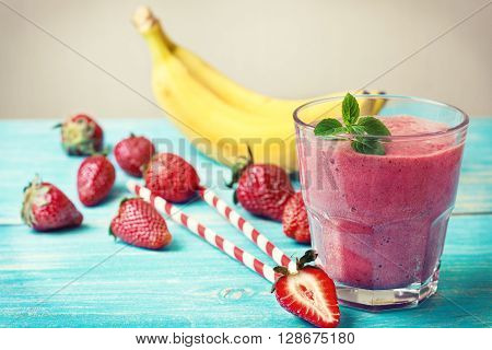 smoothie with banana and strawberry in the glass fresh strawberries and bananas on the wooden background (toning)