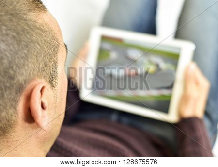 a young caucasian man lying on the couch watches car racing in streaming in his tablet computer