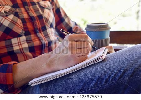 closeup of a young caucasian man wearing jeans and a plaid shirt writing with a pen in a notebook