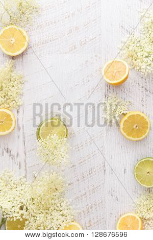 Elderflower cordial and ingredients.  Homemade elder flower cordial with lemons and elderflowers  on a rustic table. Top view with copyspace in the middle