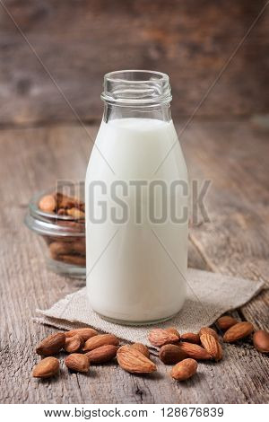 almond milk in a glass bottle almonds on old wooden background