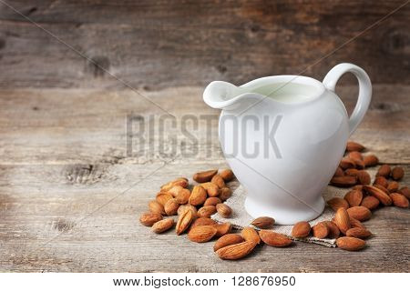 almond milk in the jug of milk almond on the old wooden background