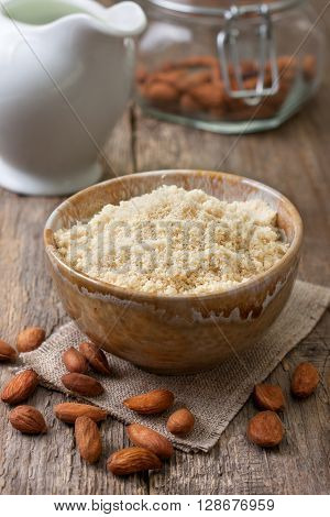 almond flour in a ceramic bowl almonds and almond milk in a jug on old wooden background