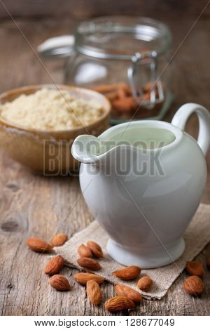 almond milk in the jug of milk crushed almonds and almond on the old wooden background