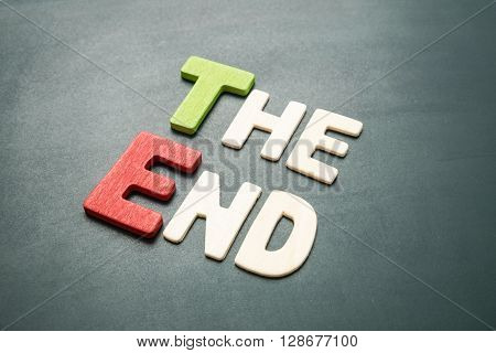 The End - colorful wording on blackboard. The End uppercase letters made from wood.