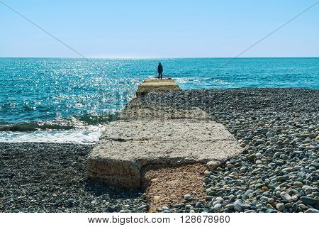 Breakwater with a silhouette of the person and pebble beach with sea views