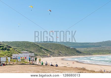 KNYSNA SOUTH AFRICA - MARCH 3 2016: Paragliders in the air with spectators watching at a beach in Buffelsbaai (Buffalo Bay) a small town in the Knysna municipal area