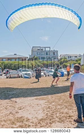 KNYSNA SOUTH AFRICA - MARCH 3 2016: A paraglider landing between people at a beach in Buffelsbaai (Buffalo Bay) a small town in the Knysna municipal area
