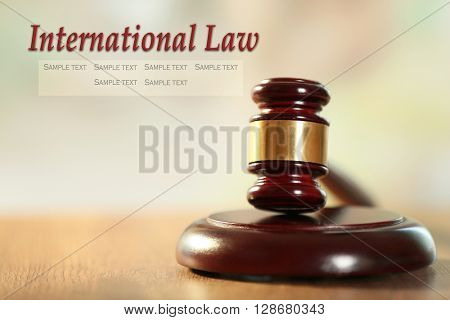 Wooden judges gavel on wooden table, close up. International law concept