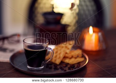 Glass cup of coffee with waffles on dark table