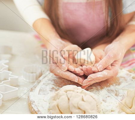 Mother and daughter kneading a dough.