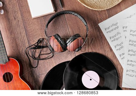 Small guitar, headphones, vinyl records and music sheets on wooden surface, top view