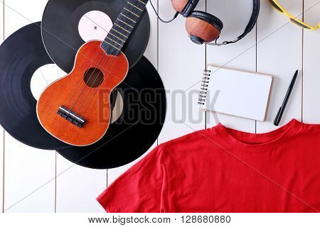 Musical equipment and clothes on wooden surface, top view