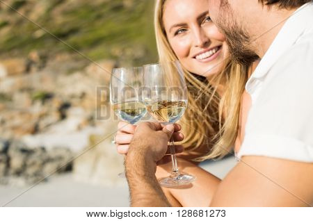 Happy romantic couple enjoying glass of white wine on the beach. Cheerful couple toasting wineglasses for celebrating anniversary. Close up of couple toasting with white wine outdoor.