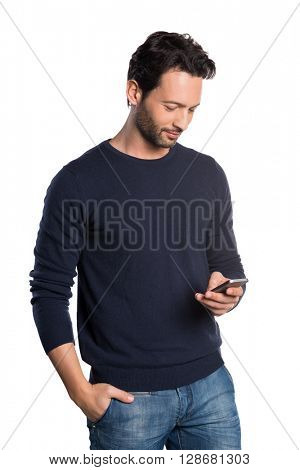 Relaxed young man in casual typing message on smartphone. Portrait of a happy man using cell phone isolated on white background. Handsome guy checking mail. Communicaton and connection concept.