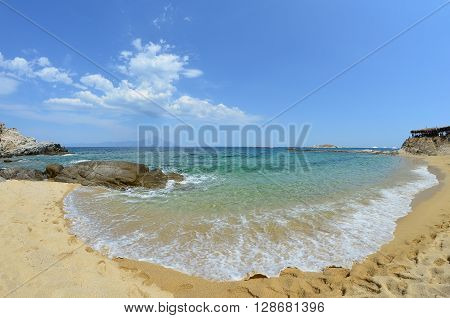 Hidden sandy beach with white waves in a sunny windy summer day with mountain Athos in background Greece Sithonia