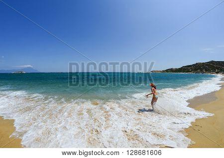 Young girl running running through shallow water of golden sandy beach Greece Sithonia