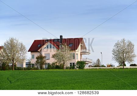 Residential private house with flowering trees. Green field in the foreground against a blue sky.