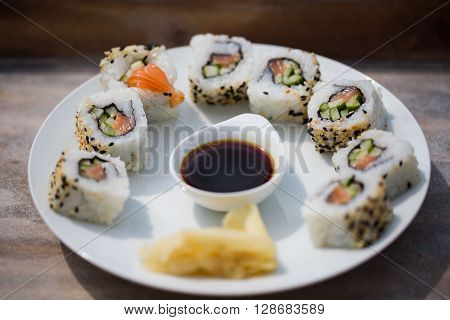 Sushi nicely on porcelain plate, on a table