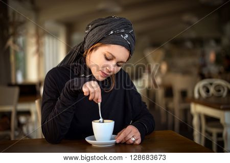 Beautiful Arab girl is drinking coffee in a cafe. She sits at a table in a restaurant, and drink coffee in soft sunlight from the window.