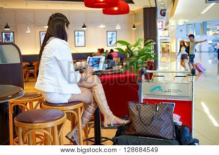 HONG KONG - JUNE 04, 2015: woman surf internet in Pacific Coffee cafe. Pacific Coffee Company is a Pacific Northwest U.S.- style coffee shop group originating from Hong Kong
