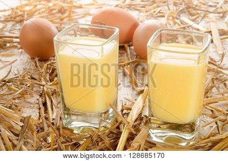 home made egg liqueur shot glass and fresh eggs in the straw