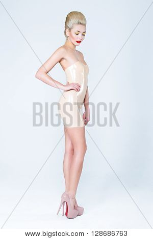 Blonde young woman in pastel latex dress