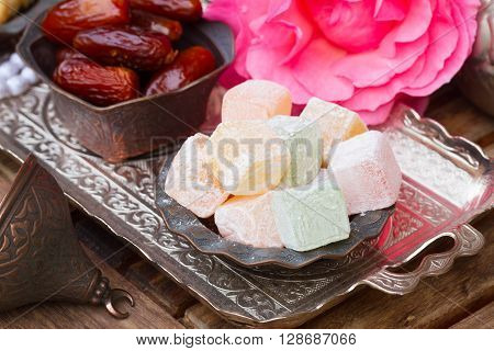 Lumps of Lokum or Turkish Delight in a tradition copper vase on oriental  metal tray