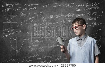 Cute boy looking through magnifying glass against blackboard background