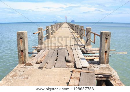 old dilapidated construction wooden and cement bridge road in a sea