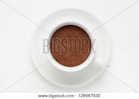 Coffee cup full of ground coffee on saucer against white background, view from above