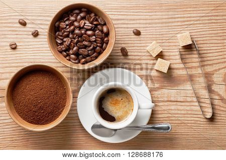Coffee beans, ground coffee and cup of brewed coffee on rustic wooden table with sugar tongs, cane sugar cubes and coffee beans, view from above