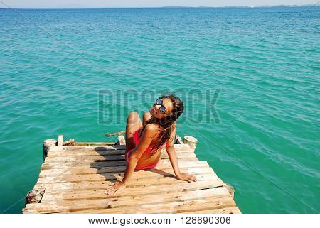 young caucasian teenage girl in swimsuit with long hair sitting on the wooden pier by blue ionian sea greece