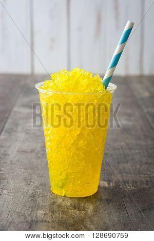 Fresh lemon slushie in glass on wood