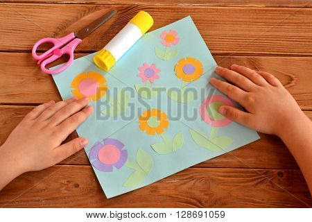 Applique with paper flowers. Child put his hands on a desk. Child made crafts. Scissors, glue