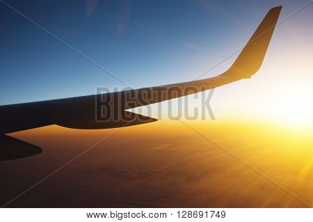 Airplane wing and rising sun
