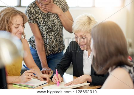 Candid picture of a female boss and business team collaborating. Filtered serie with light flares, bokeh, warm sunny tones.