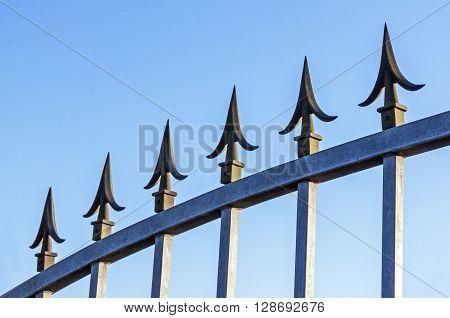 Spikes On Galvanised Gate Against Blue Sky